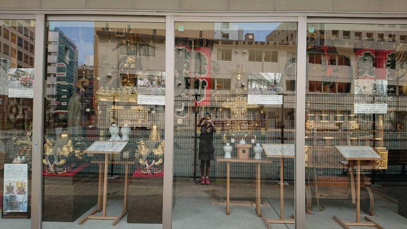茅場町にあるまちかど資料館、ガラスに写真を撮る私が写っています。